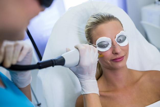 彼女の顔にレーザー脱毛治療を受ける女性