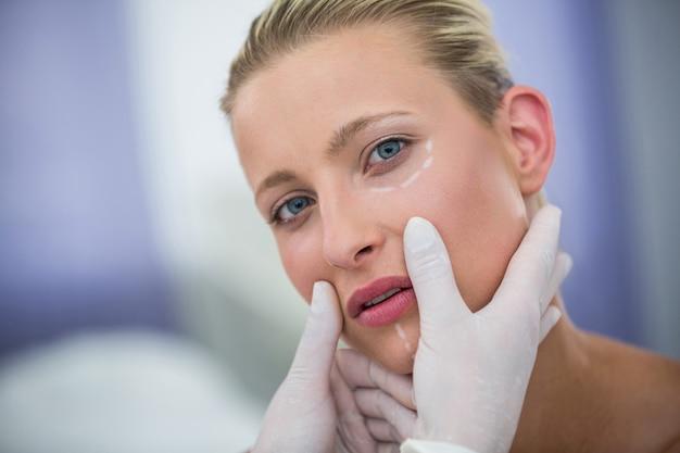 美容治療のために女性患者の顔を調べる医師