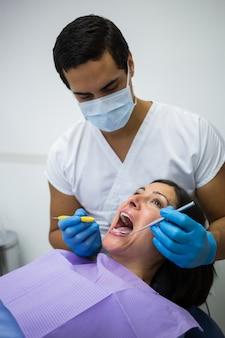歯科医が女性患者の歯を調べる