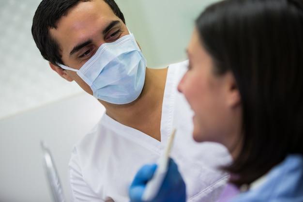 歯科医が歯の色合いのモデルで女性患者を調べる