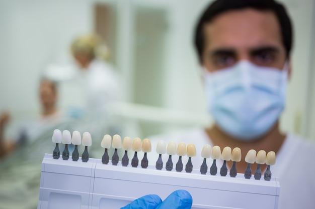 Стоматолог, держа зубы оттенков