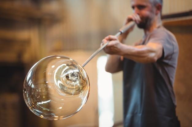 ブローパイプでガラスを成形するグラスブロワー