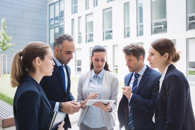 Бизнесмены обсуждают на цифровой планшет