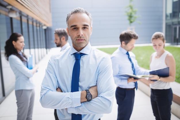 事務所ビルの外に立っている自信の実業家