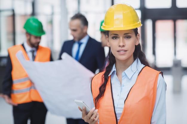 Женский архитектор держит мобильный телефон