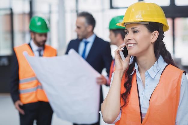 携帯電話で話している女性の建築家