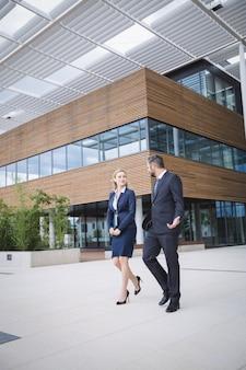 Бизнесмен гуляя с коллегой вне офисного здания