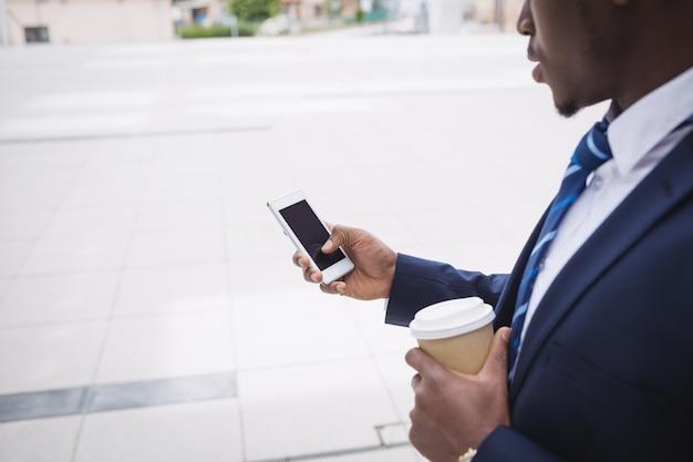 コーヒーカップを押しながら携帯電話を使用するビジネスマン