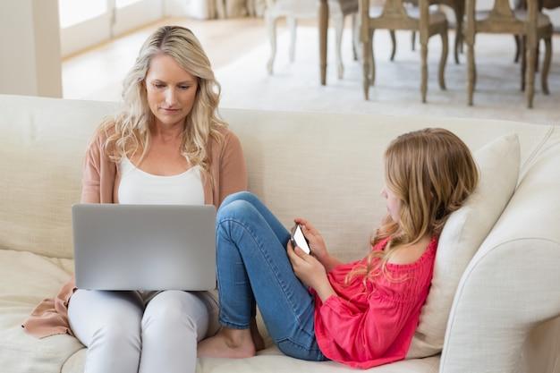 Мать и дочь, используя ноутбук и мобильный телефон