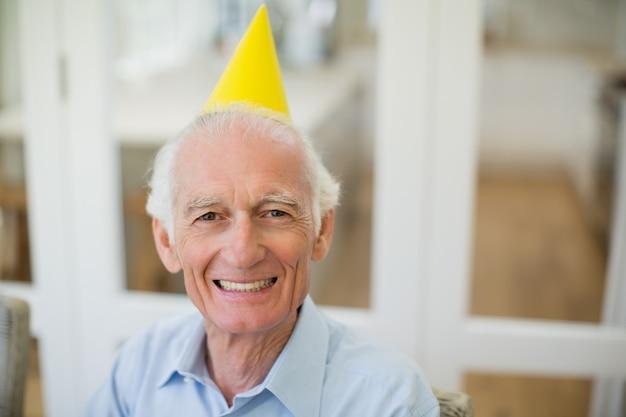 パーティーハットと年配の男性の笑顔