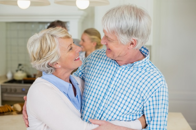 キッチンで顔を見ながらロマンチックな年配のカップル