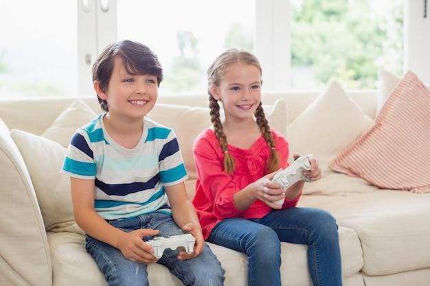 Братья и сестры играют в видеоигры в гостиной