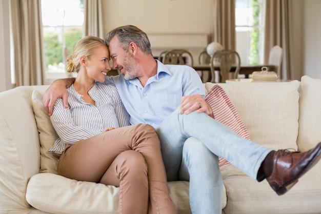 ロマンチックなカップルはリビングルームで腕をソファーに座っていた