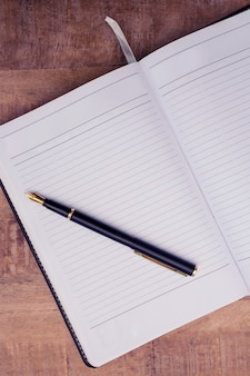 Высокий угол обзора пера на открытой книге за столом
