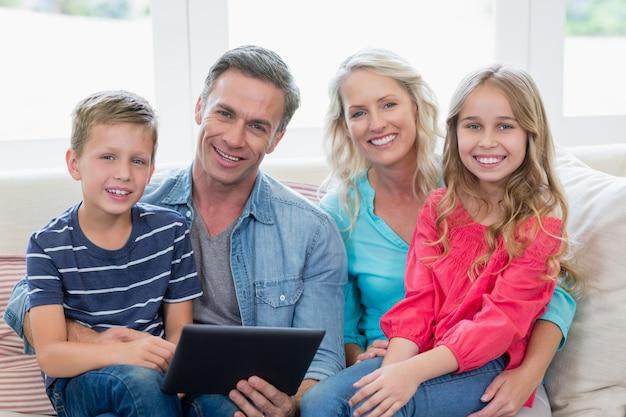 リビングルームでデジタルタブレットでソファーに座っていた親と子の笑顔