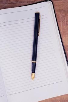 Крупный план пера на открытой книге за столом