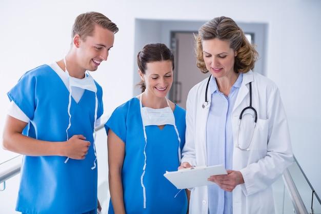 病院の廊下でクリップボードと議論する医師