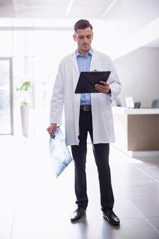 廊下にクリップボードを持って立っている医者