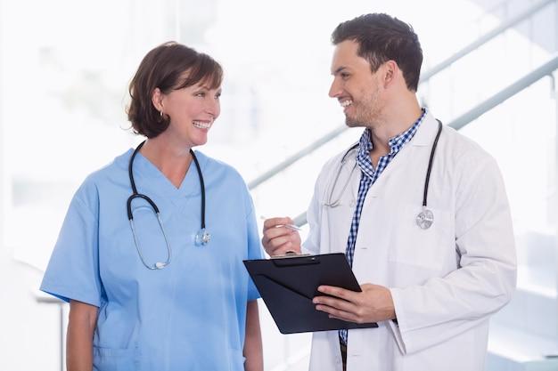 看護師と医師が廊下でクリップボードを議論