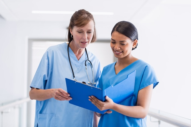 クリップボードを介して議論する看護師と医師