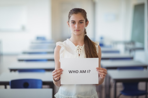 教室でテキストサインインホワイトペーパーを保持している女子高生