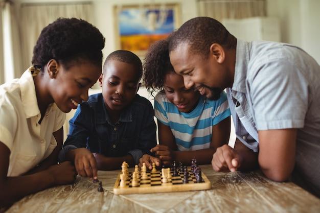 家族が自宅のリビングルームでチェスを一緒に遊んで