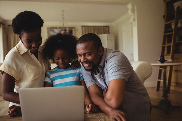 Родители и дочь, используя ноутбук в гостиной