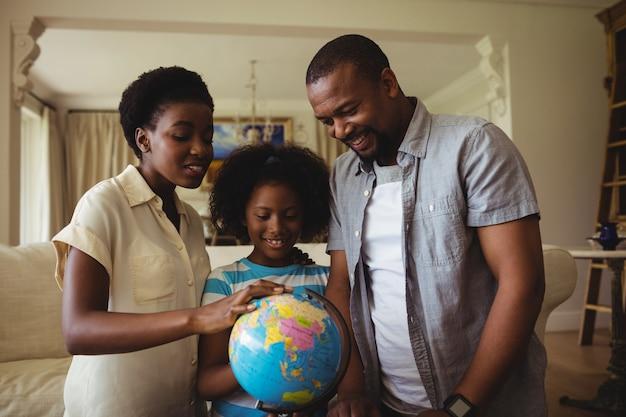 両親と娘のリビングルームで世界中を見て