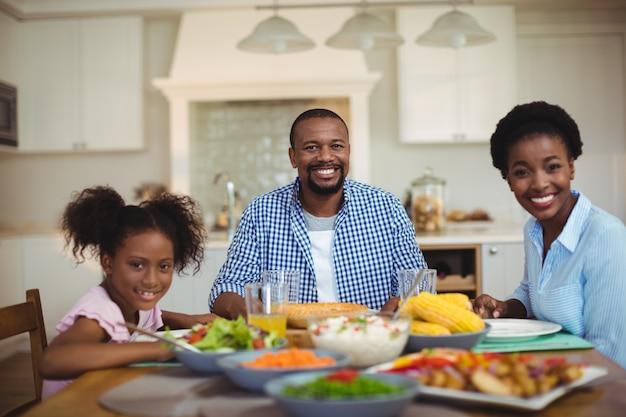 Портрет семьи обедают на обеденном столе у себя дома