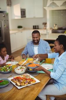 自宅のダイニングテーブルで食事を持っている家族