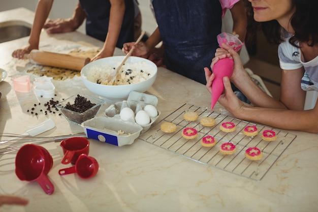 母親と子供たちはキッチンでクッキーを準備します