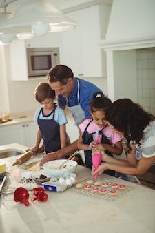 キッチンでクッキーを準備する幸せな家族