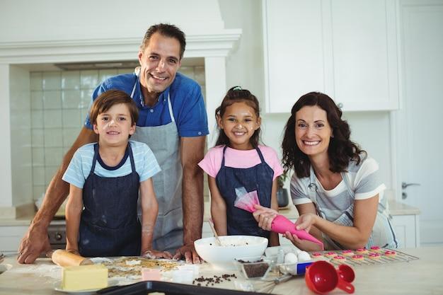 キッチンでクッキーを準備する幸せな家族の肖像画
