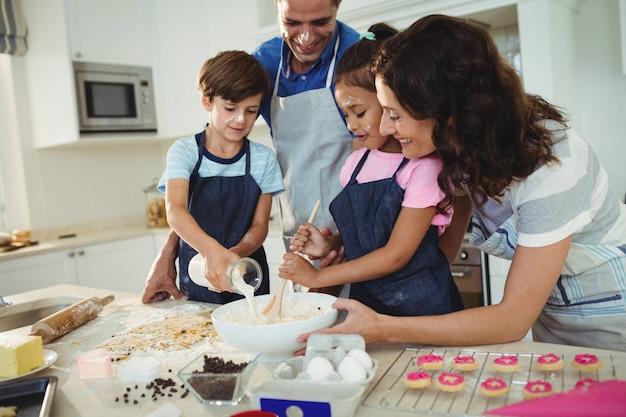 Счастливая семья готовит печенье на кухне