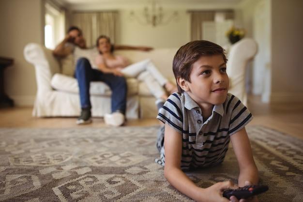 Родители и сын смотрят телевизор в гостиной