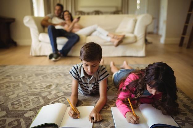 敷物の上に横たわっている間宿題をしている子供