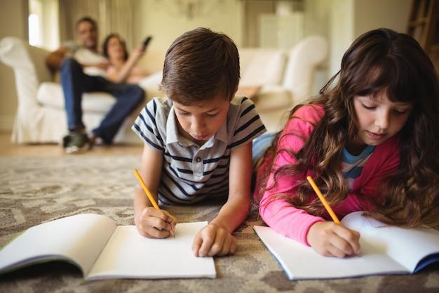 敷物の上に横たわっている間子供の宿題