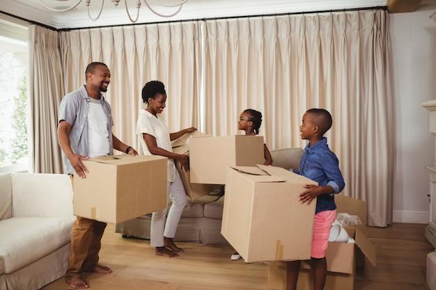 リビングルームで段ボール箱を保持している親と子供