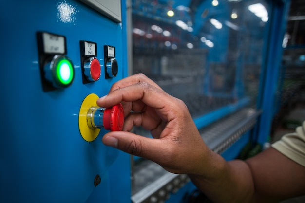 Руки фабричного рабочего поворачивают ручку управления на доске