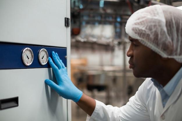 Заводской инженер контролирует манометр на заводе