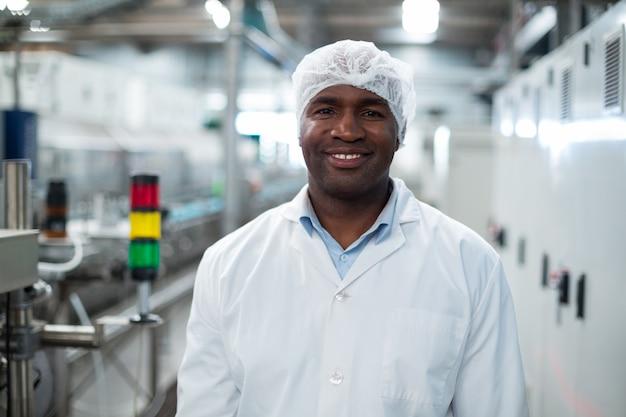 Улыбающийся заводской инженер, стоящий в бутылочной фабрике