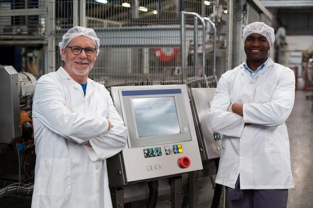 Портрет двух заводских инженеров, стоящих со скрещенными руками