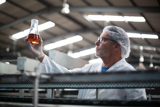 工場エンジニアが飲み物のサンプルをチェック