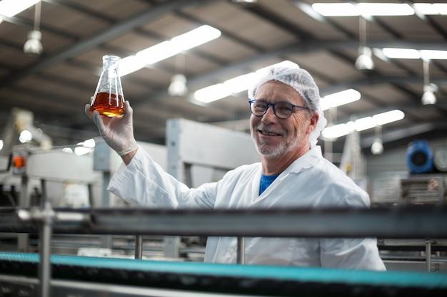 飲み物のサンプルを保持している工場エンジニア