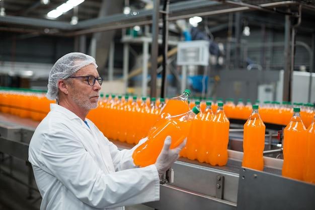 ジュースのボトルを調べる工場エンジニア