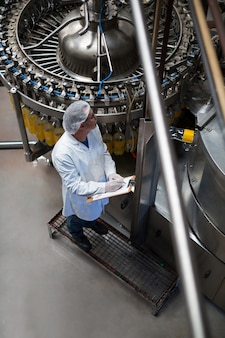 Инженер-технолог контроля заполнил бутылку сока на производственной линии