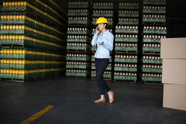 携帯電話で話している女性の工場労働者
