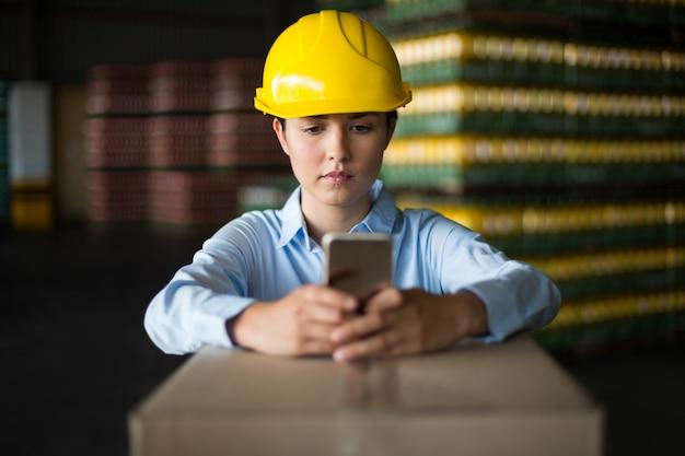 Работница фабрики с помощью мобильного телефона