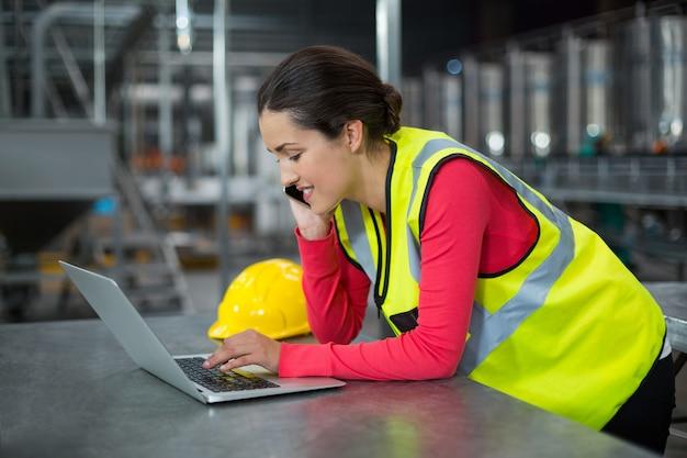 携帯電話で話しながらラップトップを使用して女性の工場労働者