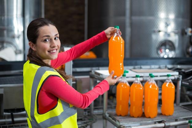 ジュースのボトルを調べる女性工場労働者